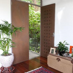シドニーの中サイズの両開きドアおしゃれな玄関ドア (ピンクの壁、濃色無垢フローリング、茶色いドア) の写真