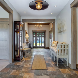 Mid-sized arts and crafts slate floor and multicolored floor entryway photo in Grand Rapids with white walls and a dark wood front door