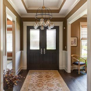 Idee per un ingresso american style di medie dimensioni con pareti arancioni, parquet scuro, una porta a due ante, una porta in legno scuro e pavimento marrone