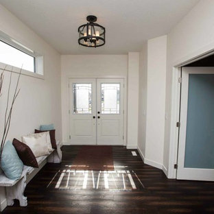 Entryway - mid-sized rustic dark wood floor entryway idea in Edmonton with white walls and a white front door