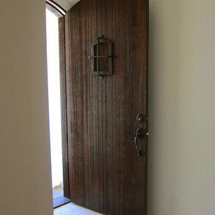 サンタバーバラの中くらいの片開きドア地中海スタイルのおしゃれな玄関ドア (白い壁、トラバーチンの床、濃色木目調のドア、黄色い床) の写真