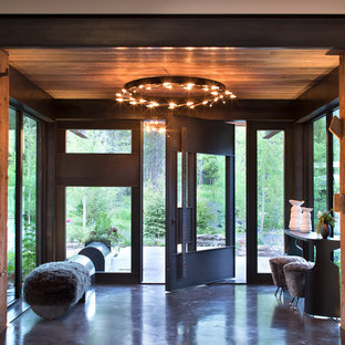 Design ideas for a rustic foyer in Other with concrete flooring, a pivot front door, a glass front door and grey floors.