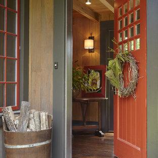Immagine di un ingresso o corridoio rustico con una porta rossa