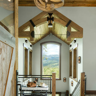 Inspiration for a rustic travertine floor and brown floor entryway remodel in Denver with white walls and a medium wood front door