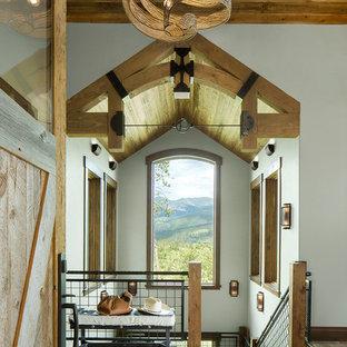 Modelo de hall rústico con suelo de travertino, suelo marrón, paredes blancas, puerta simple y puerta de madera en tonos medios