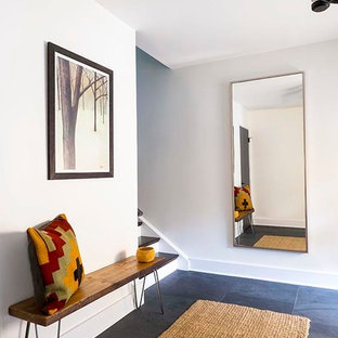 Entryway - mid-sized rustic slate floor entryway idea in New York with white walls and a gray front door