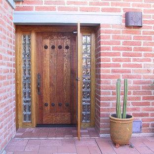 Esempio di una porta d'ingresso stile rurale di medie dimensioni con pareti rosse, una porta singola e una porta in legno bruno