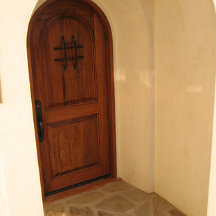 Inspiration for a mid-sized mediterranean limestone floor and beige floor entryway remodel in Santa Barbara with yellow walls and a medium wood front door