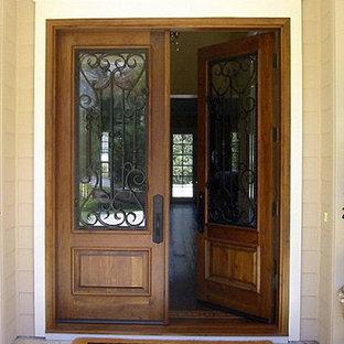 Modelo de puerta principal clásica, grande, con puerta doble, puerta de madera oscura, paredes beige y suelo de granito