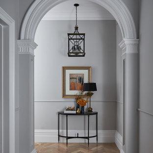 Inredning av en klassisk hall, med grå väggar, mellanmörkt trägolv och brunt golv