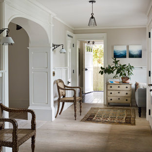 Foyer - mid-sized farmhouse limestone floor and beige floor foyer idea in New York with gray walls and a white front door
