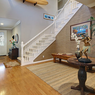 Mid-sized island style medium tone wood floor and brown floor entryway photo in Orange County with beige walls and a white front door