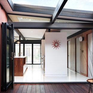 Foto di un piccolo ingresso moderno con pareti rosse, pavimento in vinile, una porta in vetro e pavimento bianco
