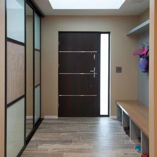 サンフランシスコの中サイズの片開きドアコンテンポラリースタイルのおしゃれな玄関ロビー (青い壁、磁器タイルの床、濃色木目調のドア) の写真
