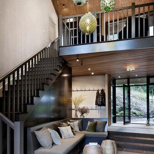 Inspiration pour un grand hall d'entrée chalet avec un sol en ardoise et un sol noir.
