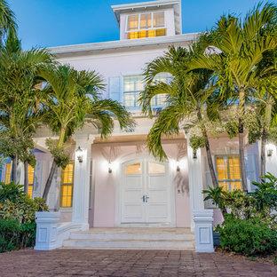 他の地域の巨大な両開きドアビーチスタイルのおしゃれな玄関ドア (ピンクの壁、トラバーチンの床、白いドア、ベージュの床) の写真