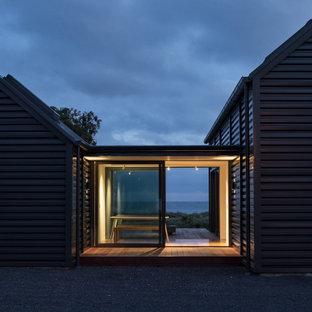 Cette image montre une porte d'entrée marine de taille moyenne avec un mur noir, un sol en bois brun, une porte coulissante, une porte en verre, un sol marron et un plafond en lambris de bois.
