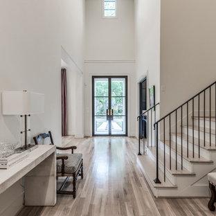 ヒューストンの巨大な両開きドアトランジショナルスタイルのおしゃれな玄関ロビー (白い壁、淡色無垢フローリング、金属製ドア、ベージュの床) の写真