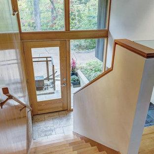 Cette photo montre un hall d'entrée rétro avec un mur blanc, un sol en liège, une porte simple, une porte en bois clair et un sol beige.