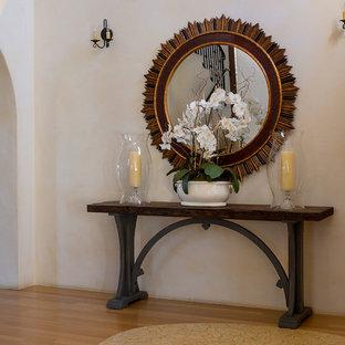 Imagen de puerta principal mediterránea, grande, con paredes beige, suelo de bambú, puerta simple y puerta de madera oscura