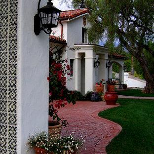 Exemple d'une porte d'entrée méditerranéenne de taille moyenne avec un mur blanc, une porte simple, une porte métallisée, un sol en brique et un sol rouge.