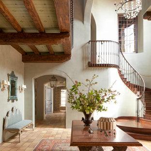 Cette image montre un grand hall d'entrée méditerranéen avec un mur blanc et un sol en brique.