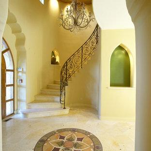 На фото: огромное фойе в средиземноморском стиле с желтыми стенами с