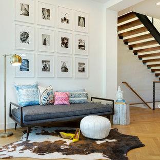 Ejemplo de entrada contemporánea con paredes blancas y suelo de madera en tonos medios