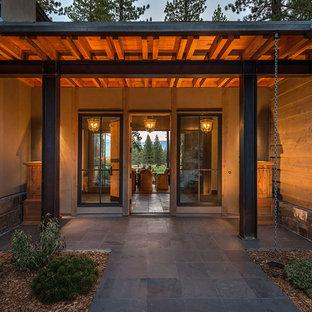 Inspiration pour une grand porte d'entrée chalet avec une porte simple, une porte en bois brun, un mur marron et un sol en ardoise.