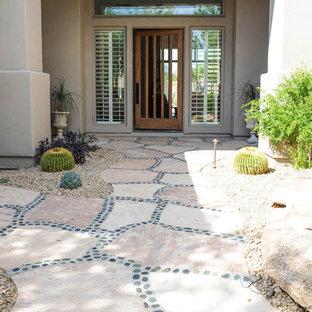 Cette photo montre une grand porte d'entrée sud-ouest américain avec un mur beige, une porte simple, un sol en carrelage de porcelaine, une porte en bois clair et un sol beige.