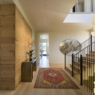 Example of a mid-sized trendy light wood floor and beige floor foyer design in San Francisco with white walls