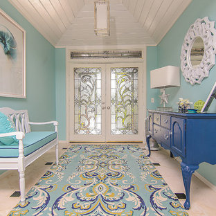 Inspiration for a small coastal travertine floor entryway remodel in Miami with blue walls and a white front door
