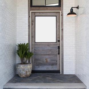 オレンジカウンティの中サイズの片開きドアビーチスタイルのおしゃれな玄関ドア (白い壁、スレートの床、木目調のドア、青い床) の写真