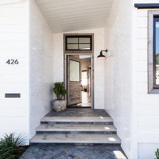 Неиссякаемый источник вдохновения для домашнего уюта: входная дверь среднего размера в морском стиле с белыми стенами, одностворчатой входной дверью, входной дверью из дерева среднего тона, полом из сланца и синим полом