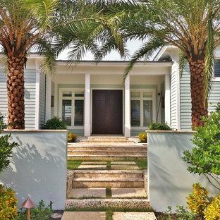 マイアミの両開きドアトロピカルスタイルのおしゃれな玄関 (濃色木目調のドア) の写真