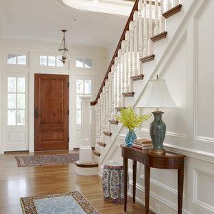 ボストンの広い片開きドアトラディショナルスタイルのおしゃれな玄関ロビー (木目調のドア、白い壁、無垢フローリング、茶色い床) の写真