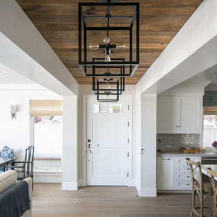 Beach style light wood floor entryway photo in Orange County with gray walls and a white front door