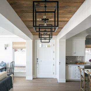 Diseño de distribuidor marinero con paredes grises, suelo de madera clara, puerta tipo holandesa y puerta blanca
