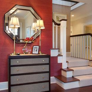 На фото: фойе среднего размера в стиле фьюжн с красными стенами, темным паркетным полом, одностворчатой входной дверью, входной дверью из темного дерева и коричневым полом с