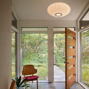 Стильный дизайн: прихожая в стиле ретро с одностворчатой входной дверью, входной дверью из дерева среднего тона и серым полом - последний тренд