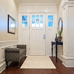 Inspiration för mellanstora klassiska hallar, med beige väggar, mörkt trägolv, en skjutdörr, en vit dörr och brunt golv