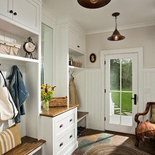 Cette image montre une entrée rustique avec un vestiaire, une porte simple, une porte en verre et un mur blanc.