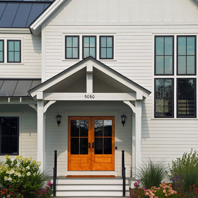 Example of a cottage entryway design in Boston with a glass front door