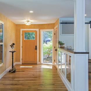 Ejemplo de vestíbulo tradicional renovado, grande, con parades naranjas, suelo de madera clara, puerta simple, puerta de madera clara y suelo marrón