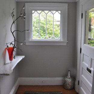 Idéer för en liten klassisk farstu, med grå väggar, ljust trägolv, en enkeldörr och en vit dörr