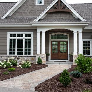 Imagen de puerta principal de estilo americano, de tamaño medio, con paredes marrones, puerta doble y puerta de madera oscura