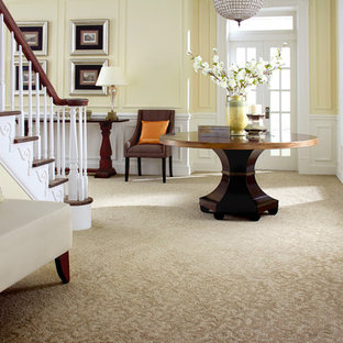 Entryway - mid-sized traditional carpeted and beige floor entryway idea in Orange County with yellow walls and a glass front door