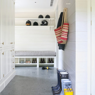Inspiration for a beach style gray floor mudroom remodel in New York with white walls