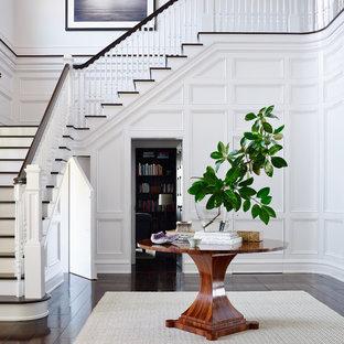 Пример оригинального дизайна: большое фойе в викторианском стиле с белыми стенами и темным паркетным полом
