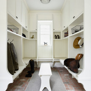 Inspiration for a timeless brick floor and pink floor mudroom remodel in New York with white walls and a white front door
